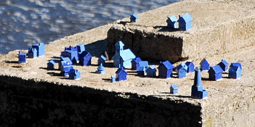 Miniature blue town popped up on one of the old stone piers in view of pedestrian bridge to Belle Isle