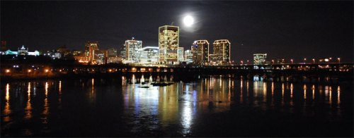 View from the pedestrian bridge of the full moon over the downtown skyline