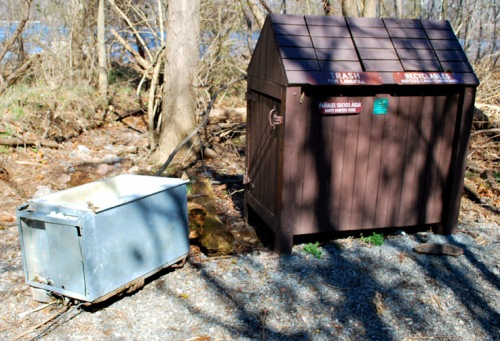 The abandoned refrigerator at Pony Pasture Rapids has been pulled from the James River and left beside the trash recepticle along the River Trail